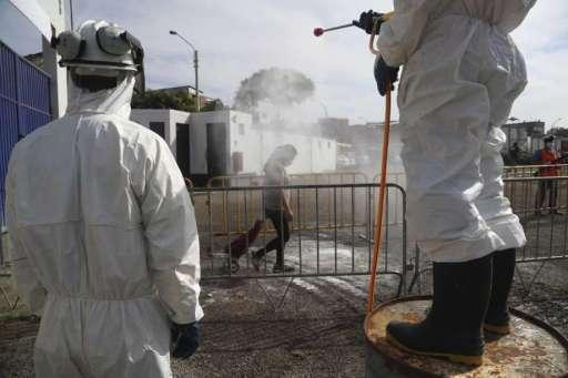 Los compradores son rociados por un desinfectante al ingreso al reciento